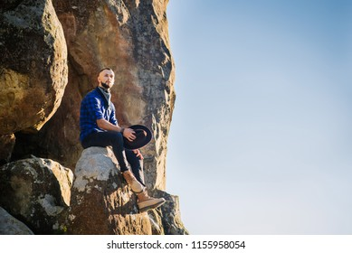 A man in the hat sitting high on the rocks at the blue sky background