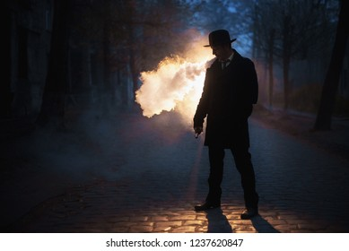 The man in hat smoke an electronic cigarette on the dark background outdoor. Vaponizer concept