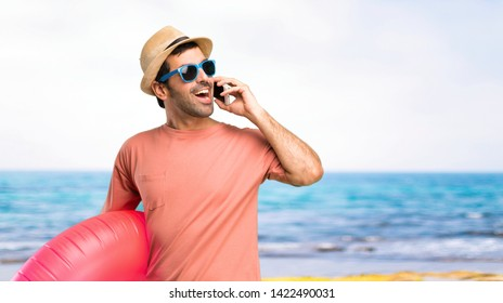 Man with hat and sunglasses on his summer vacation talking to mobile at the beach