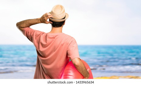Man with hat and sunglasses on his summer vacation on back position looking back while scratching head at the beach