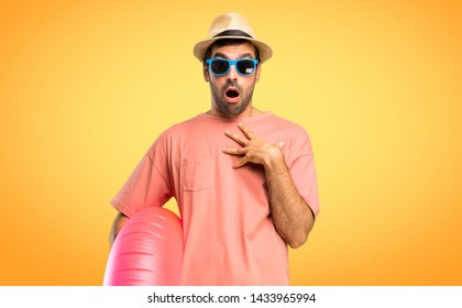 Man with hat and sunglasses on his summer vacation surprised and shocked while looking right. Expressive facial emotion on orange background