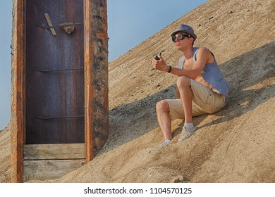A man in a hat, vest and steampunk goggles sitting in the middle of the desert on a large sand dune, next to an incomprehensible rusty construction, and smokes a pipe. Post-apocalyptic cosplay