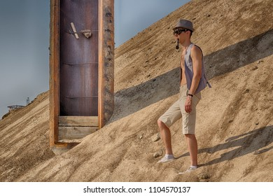 A man in a hat, vest and steampunk goggles stands in the middle of the desert on a large sand dune, next to an incomprehensible rusty construction, and smokes a pipe. Post-apocalyptic cosplay