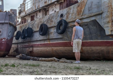 A man in a hat and waistcoat stands with his back to the viewer and looks at an old rusty ship covered with corrosion