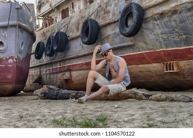 A man in a hat, waistcoat and Steampunk goggles is smoking a pipe against the background of an old rusty ship covered with corrosion. Post-apocalyptic cosplay