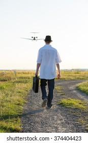 A man with a hat walks below a landing aircraft
