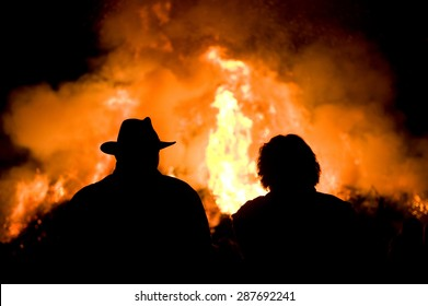 Man with a hat and a woman are watching a huge bonfire, a tradition with easter in North-West Europe.