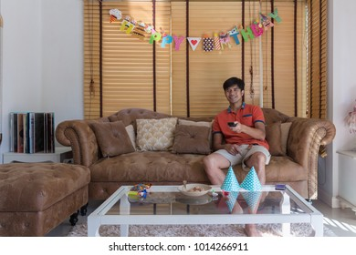 Man have relax time with sit on brown vintage sofa and hold TV remote control