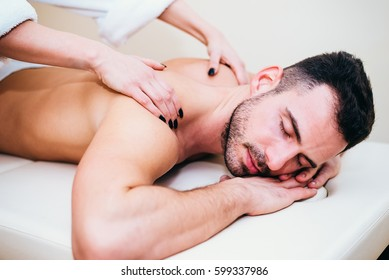 Man having back massage from masseur in spa