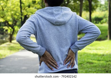 Man having a backache. the man with warm shirt have a backache in the park. young man having a pain in lower back when play sport. a man has low back pain.