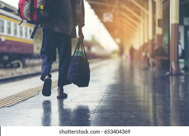 Man is having a backpack behind his back with a cloth bag, walking beside a platform at train station. He's wearing an old pale long pant and choosing a cheaper transportation to save his money.