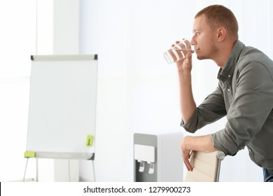 Man having break near water cooler at workplace. Space for text