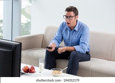 Man having breakfast while watching something shocking on tv