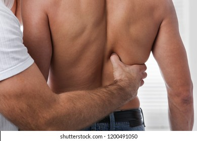 Man having chiropractic back adjustment. Osteopathy, acupressure, sport injury rehabilitation concept