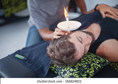man having an ear candle therapy (soft focus on his eyes)