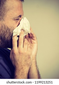 Man having flu, sneezing into hygienic tissue. Guy being sick, allergic blowing his nose.