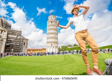 Man having fun with the famous leaning tower in Pisa old town in Italy. Happy vacations in Italy