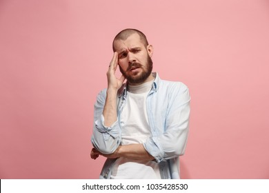 Man having headache. Isolated on pink background. Business man standing with pain isolated on trendy pink studio background. Male half-length portrait. Human emotions, facial expression concept. Front
