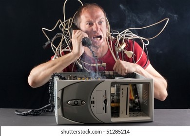 man having his computer burning phoning technical support for help