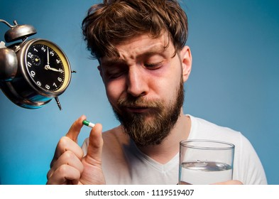 Man having insomnia concept, thinking about sleep pill while holding glass of water, alarm clock near his head