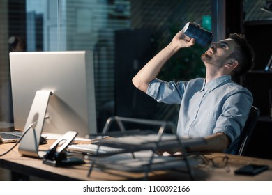 Man having lack of caffeine and coffee finished while sitting at table with computer working late at night in office.