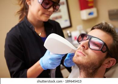 Man Having Laser Treatment At Beauty Clinic