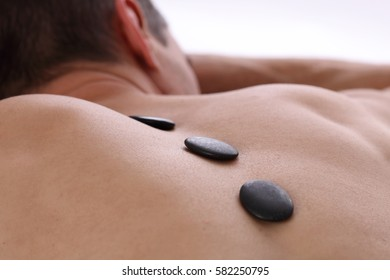 Man having massage with volcanic rocks. Relaxation, body care treatment, spa, wellness concept.
