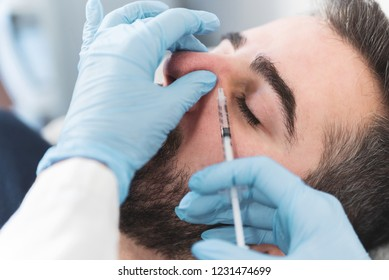 Man having nose fillers done at medical clinic.
