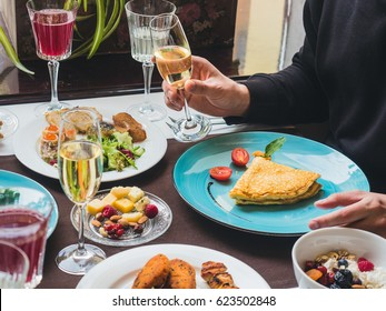 Man having an omelette on a blue plate, glass of sparkling wine in hand and plates with greens and other food on the table. Breakfast (brunch) buffet in a luxury hotel. Horizontal orientation