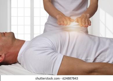 Man having reiki energy healing treatment ,holistic care, alternative medicine concept.