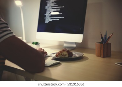Man having snack while working with computer late in evening