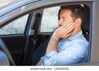 Man having toothache while driving car