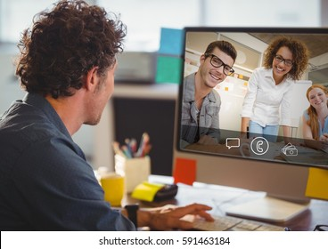 Man having video call with colleagues on computer in office