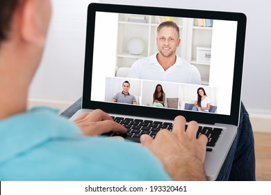 Man having video conference with friends on laptop at home