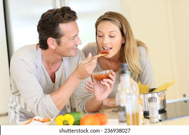 Man having woman tasting tomato sauce