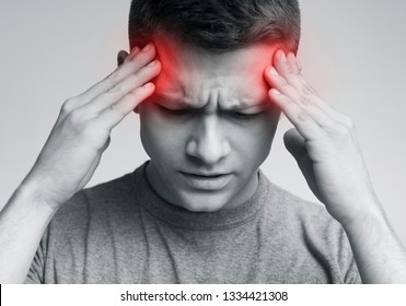 Man with headache touching his temples, emotional black and white photo with red sore zones