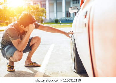 A man headache when car breakdown and wheel flat tire on the road in the city.