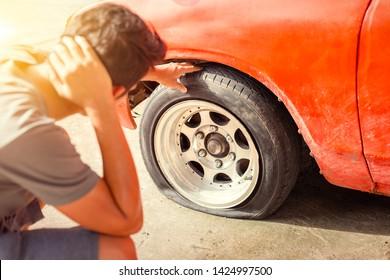 A man headache when car breakdown and wheel flat tire in parking