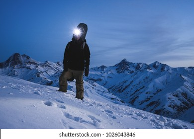 Man with headlamp and backpack wearing ski wear standing in front of amazing winter mountain view. Traveler climb at night on the snowy mountain. Ski tour