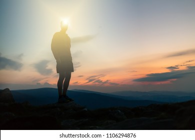 Man with headlamp celebrating sunset on mountain top. Looking at inspiring view. Trail runner, hiker or climber reached mountain peak, enjoy inspirational landscape on rocky trail Karkonosze, Poland