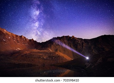 Man with headlight in the mountains at beautiful night sky with stars and Milky Way