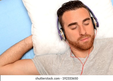 man with headphones in bed