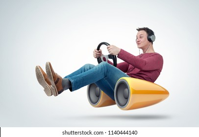 Man with headphones car driver with a steering wheel and bass speaker, concept of sound in motion