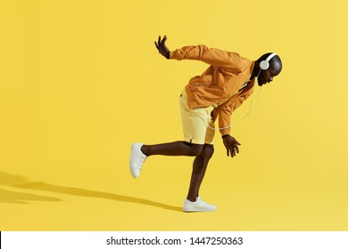 Man in headphones listening music, dancing on yellow background. Full length portrait of handsome black male model in colorful fashion clothes and white earphones in studio