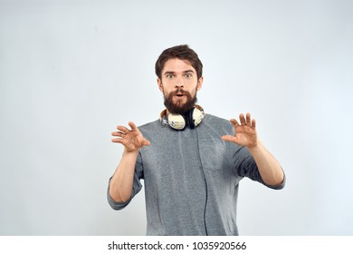 man with headphones on his neck on a light background