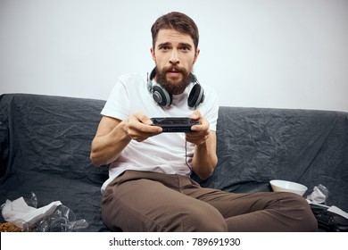 man with headphones on his neck playing the console with a joystick, litter on the couch