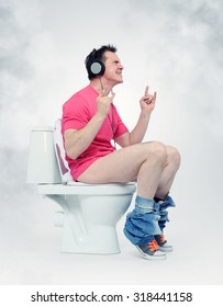 Man in headphones sitting on the toilet. Yes! Music everywhere. Situation concept