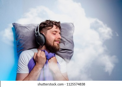 Man with headphones, sound asleep, sleeping in clouds