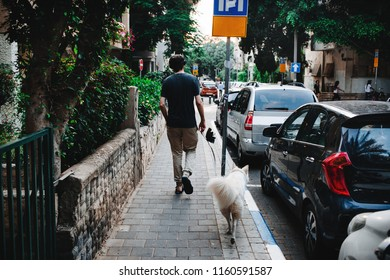 man in headphones walks the dog on the street in Tel-Aviv