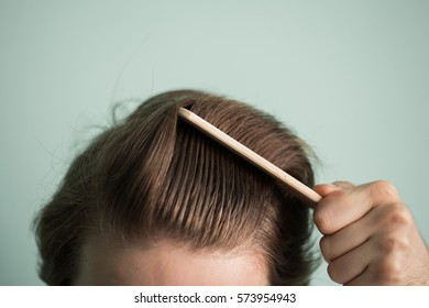man with healthy hair holding comb. clean healthy man's hair without furfur